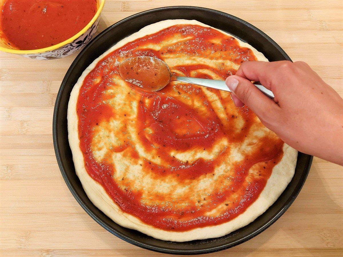 smarowanie pizzy sosem pomidorowym